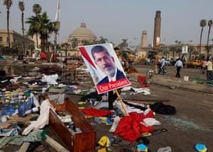 Egypt after crackdown: A man carries a poster of Egypt's ousted president Mohamed Morsi among debris from a protest camp in Nahda Square, Giza, Cairo