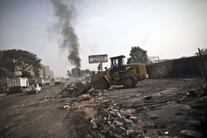 Egypt after crackdown: A tractor clears the debris in Rabaa al-Adawiya square as smoke billows in the background