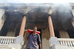 Egypt after crackdown: A man walks from a government building that was set ablaze in Giza's distri