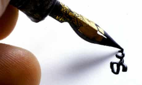 Someone signing a white piece of paper with a gold-tipped ink foundation pen