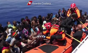 Italian coastguards help immigrants out of their boat off the coast of Lampedusa