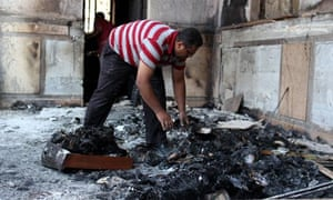 An Egyptian man clears the floor in the Prince Tadros Coptic church which was set alight in Minya