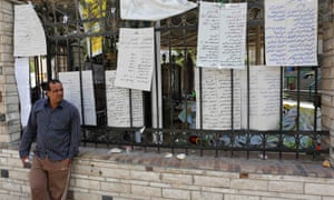 A man who lost relatives in recent violence stands near a list of names of dead members of the Muslim Brotherhood and supporters of deposed Egyptian President Mohamed Morsi at El Eyman mosque in Cairo August 16, 2013.