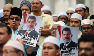 Supporters of Egypt's deposed Islamist President Mohamed Mursi and the Muslim Brotherhood display placards during a demonstration in protest of the recent violence in Egypt, in Shah Alam outside Kuala Lumpur August 16, 2013.