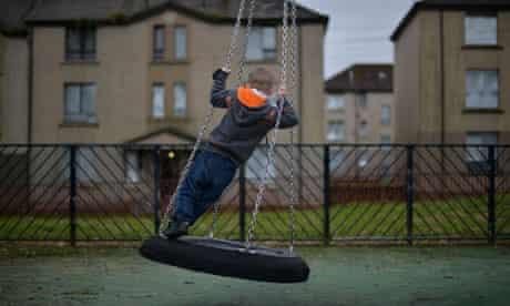 Boy on a swing outside a house