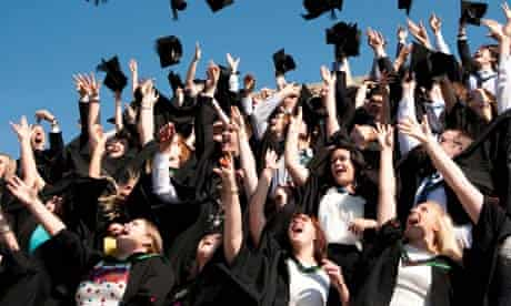 A group of university students graduating on graduation day, throwing their caps in the air, UK
