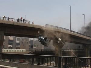 最初的描述是:一辆警车被10月6日的桥梁推开,抗议者靠近被驱逐的伊斯兰总统穆罕默德·穆尔西的支持者最大的静坐。照片:Aly Hazzaa / AP
