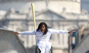Adepitan carries the Olympic Flame over the Millenium Bridge, 26 July 2012.