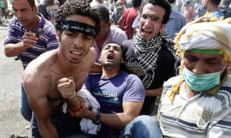 Morsi supporters carry a wounded man during clashes with security forces in Cairo, Egypt