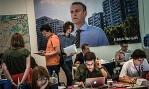 Campaign staff work next to an electoral poster of Alexei Navalny, a mayoral candidate.