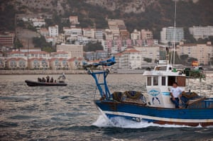 Gibraltar protests: A fisherman looks out as British police officers patrol on a boat