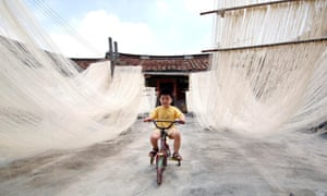 A boy rides a bicycle in between home-made rice noodles in Changting county, China.