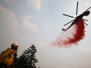 A helicopter makes a drop around a home to protect it from the Beaver Creek fire outside Ketchum, Idaho.