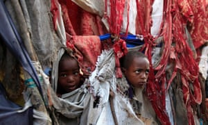 Displaced children peer through holes in the fabric used to make their temporary tent at Sayyidka camp in the Howlwadag district, south of Mogadishu, Somalia, on World Humanitarian Day.