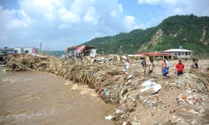 Meanwhile in Nankouqian Township, Fushun, people walk on ruins after the worst flooding in decades.