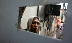 An inmate looks out from behind the gate of Labuhan Ruku prison in North Sumatra. Security forces have retaken control of the overcrowded prison in western Indonesia following a night-long riot, and have captured most of the estimated 30 convicts who escaped.