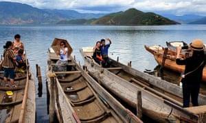 Tourists take photos beside the Lugu Lake