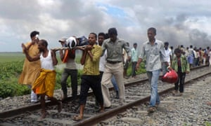 Indian villagers carry an injured person along a railway track after a train ran over a group of Hindu pilgrims at a crowded station in Dhamara Ghat, Bihar state, India. At least 37 people were killed. A mob, infuriated by the deaths, beat the driver severely and set fire to coaches, officials said.
