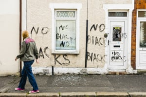 A woman looks at racist graffiti written on the walls of a house recently occupied by two Nigerian men in Belfast, Northern Ireland. Photograph: Stephen Barnes/Demotix/Corbis
