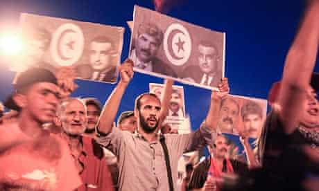Tunisian demonstrators hold pictures of assassinated opposition leader Mohamed Brahmi