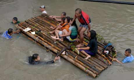 Residents of Novaleta, outside Manila, use a raft to escape the floods.