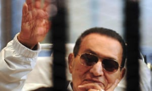 Former Egyptian President Hosni Mubarak waves to his supporters inside a cage in a courtroom at the police academy in Cairo