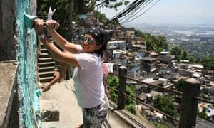 Woman painting a favela in Rio de Janeiro