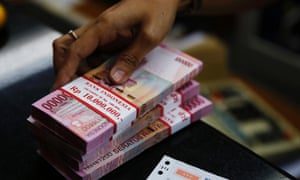 A money changer holds stacks of Indonesian rupiah notes in Jakarta. Asian markets have stabilised after a choppy start to the week.
