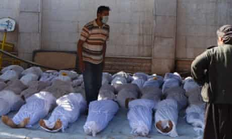 Syrian activists inspect the bodies of people they say were killed by nerve gas in the Ghouta region, in the Duma neighbourhood of Damascus, on 21 August, 2013.
