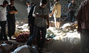 A handout image released by the Syrian opposition's Shaam News Network shows people inspecting bodies of children and adults laying on the ground as Syrian rebels claim they were killed in a toxic gas attack by pro-government forces in eastern Ghouta, on the outskirts of Damascus on 21 August, 2013.