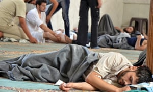 A survivor from what activists say is a gas attack rests inside a mosque in the Duma neighbourhood of Damascus. Syrian activists accused President Bashar al-Assad's forces of launching a gas attack that killed more than 200 people.