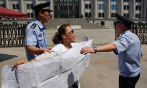 Police take away a protester outside the court in Jinan where Bo Xilai is to stand trial