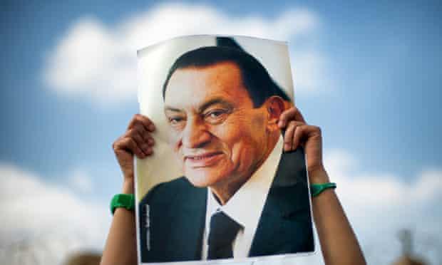 A supporter holds a poster of Egypt's former president, Hosni Mubarak