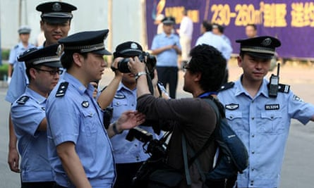 Police block a photojournalist outside the Jinan court where Bo Xilai is on trial.