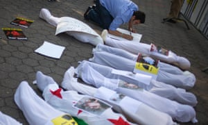 A man creates a placard next to mock corpses during a protest in front of the United Nations building in New York on 21 August, 2013.