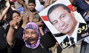 A supporter of former Egyptian president Hosni Mubarak raises up his portrait outside the Tora prison where Mubarak is detained, on 22 August, 2013, in Cairo.