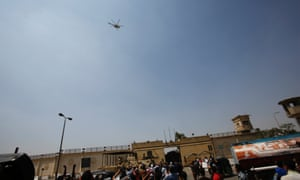 Supporters of deposed Egyptian president Hosni Mubarak gesture as the helicopter carrying him leaves the Tora prison on the outskirts of Cairo 22 August, 2013.