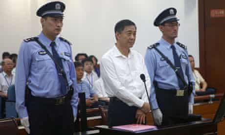 Bo Xilai is flanked by police officers during his trial