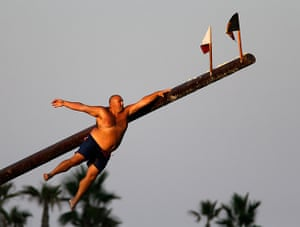 "Weekend in pictures: Valletta, Malta: A man slips off the ""gostra"", a pole covered in grease, du"