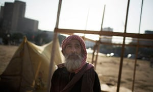 An Egyptian man stands in front of his tent in Tahrir Square