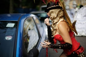 Notting Hill Carnival: A participant applies lipstick using the reflection on a car