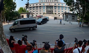 Press photographers take pictures of the convoy ferrying Bo Xilai from the Jinan courtroom