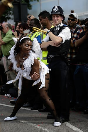 Notting Hill update: A performer dances with a policeman