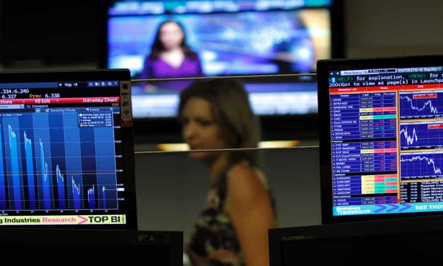 A broker walks behind screens displaying charts  in a trading room of a Portuguese bank.