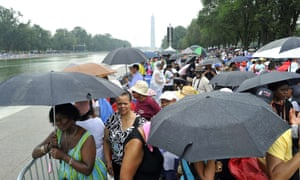 People brave rain as they arrive near at the Lincoln Memorial in Washington, DC, on August 28, 2013 to commemorate the 50th anniversary on the March on Washington.