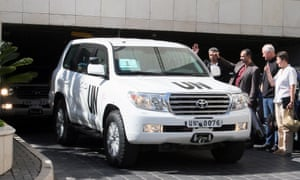 UN inspectors raise their thumbs as they watch the departure of the inspection team at the Four Seasons hotel on 27 August, 2013 in Damascus, Syria.