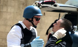 A U.N. chemical weapons expert checks a fellow expert after they ended their visit today to the site of an alleged chemical weapons attack in the Ain Tarma neighbourhood of Damascus.