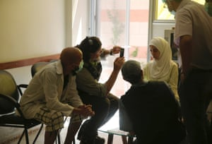 A U.N. chemical weapons expert (2nd L) takes a picture of a person affected by an apparent gas attack, at a hospital where she is being treated , in the Damascus suburb of Zamalka August 29, 2013.