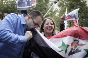 A pro-Syrian regime protester kisses a national flag as he demonstrates against French and foreign military involvement in Syria, on August 29, 2013, in Paris.