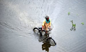 A man pushes his bicycle through floodwaters in Allahabad, India as many areas in the state are inundated from prolonged monsoon rains.